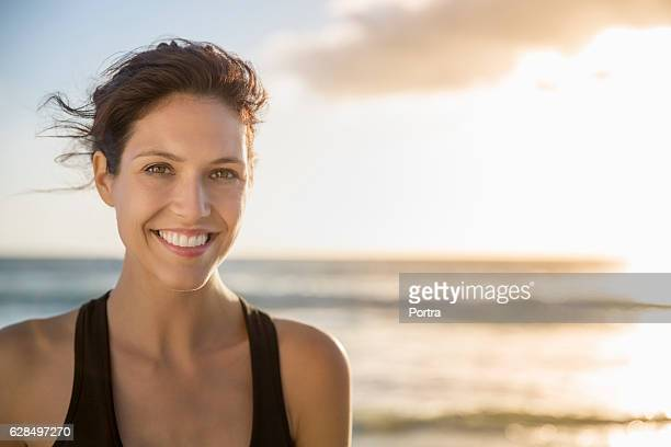 happy young woman at beach during sunset - 30 34 anos imagens e fotografias de stock