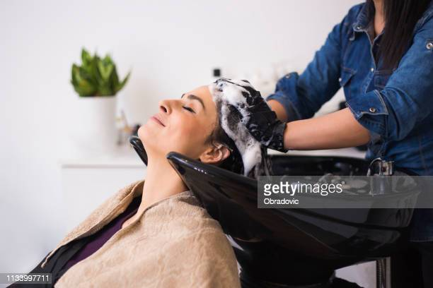 happy young woman at hair salon - hair treatment stock pictures, royalty-free photos & images