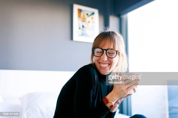 happy young woman at home drinking cup of coffee - morgen stockfoto's en -beelden