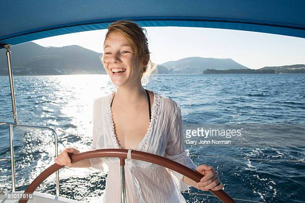 happy young woman at wheel of sailing yacht