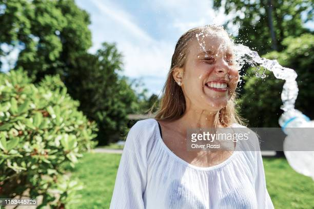 happy young woman being splashed with water in a park - rafraîchissement photos et images de collection