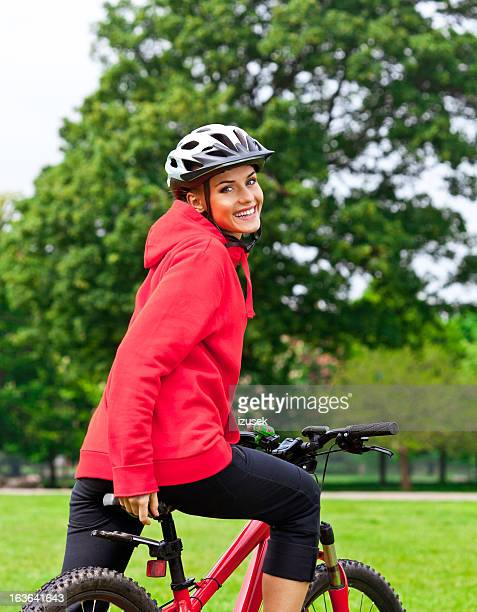 Happy young woman bicycling trough a park