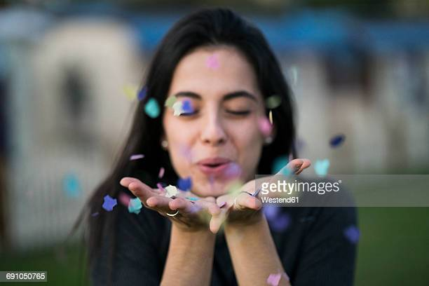 Happy young woman blowing confetti outdoors