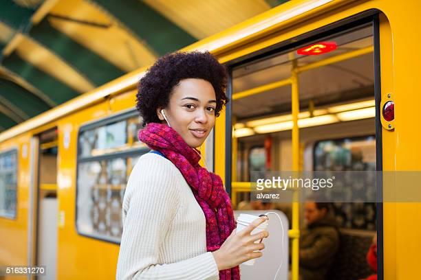 happy young woman boarding a train - metrostation stockfoto's en -beelden