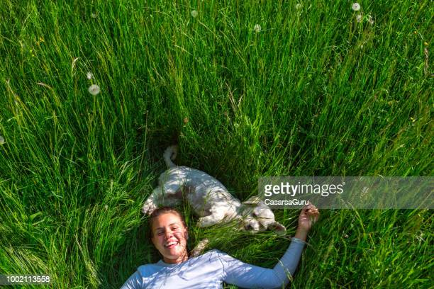 happy young woman bonding with her dog on meadow - lying down stock pictures, royalty-free photos & images