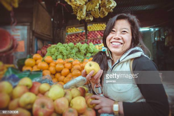 Happy young woman buying fruits at market stall.