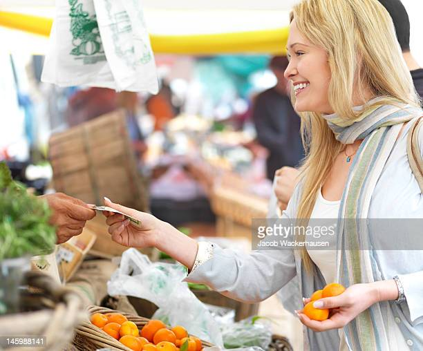 Happy young woman buying vegetables at market