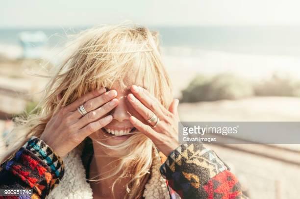 happy young woman covering eyes on beach - augen zuhalten stock-fotos und bilder