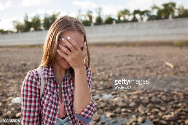 happy young woman covering her face on stony beach - verlegen stockfoto's en -beelden
