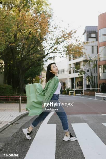 通りを渡るハッピー・ヤング・ウーマン - carefree ストックフォトと画像