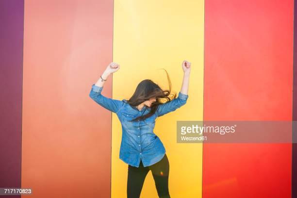 happy young woman dancing in front of colourful wall - solo una donna giovane foto e immagini stock