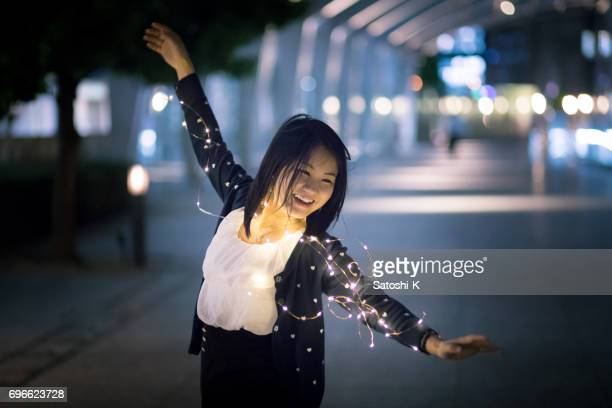 Happy young woman dancing in night urban city