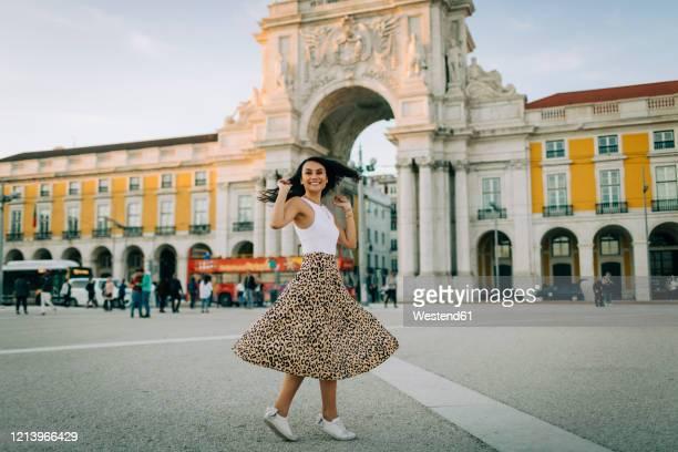 happy young woman dancing in the city, lisbon, portugal - praça do comércio imagens e fotografias de stock