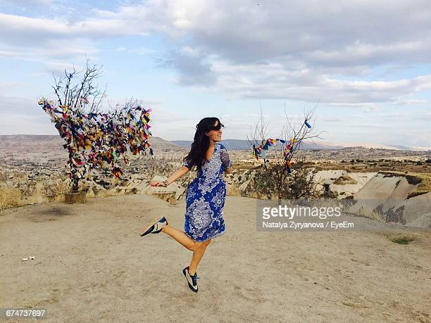 Happy Young Woman Dancing On Field Against Sky