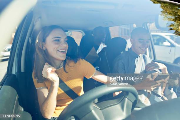 happy young woman dancing with friends in car - auto stockfoto's en -beelden