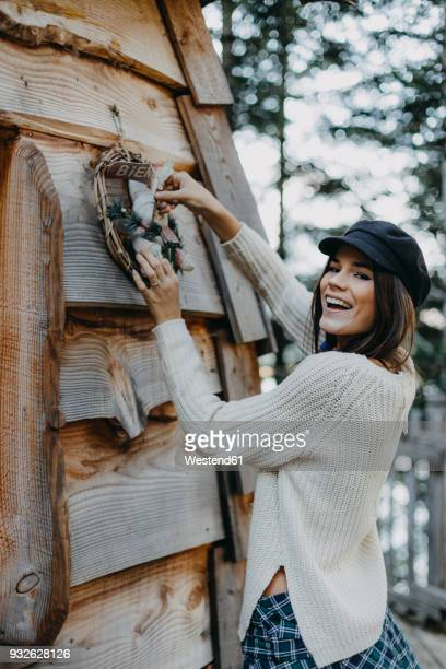 happy young woman decorating wooden house with christmas decoration - country christmas stock pictures, royalty-free photos & images