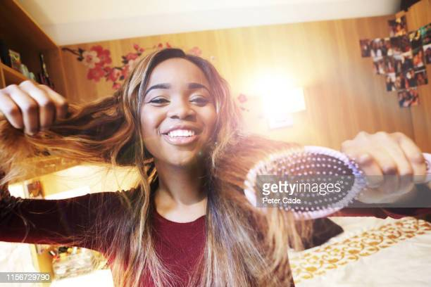 happy young woman doing her hair in her bedroom - young women stock pictures, royalty-free photos & images