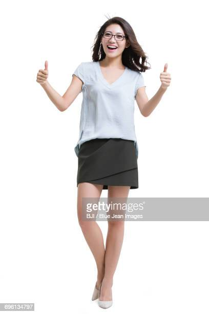 Happy young woman doing thumbs up