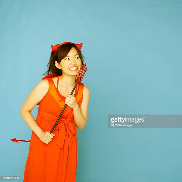 happy young woman dressed as devil - devil costume stock photos and pictures