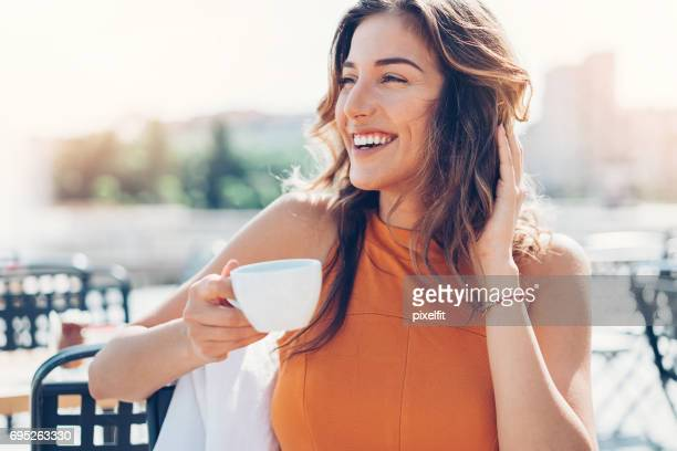 happy young woman drinking coffee outdoors - toothy smile stock pictures, royalty-free photos & images