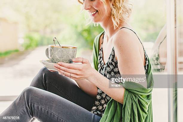 Happy young woman drinking tea