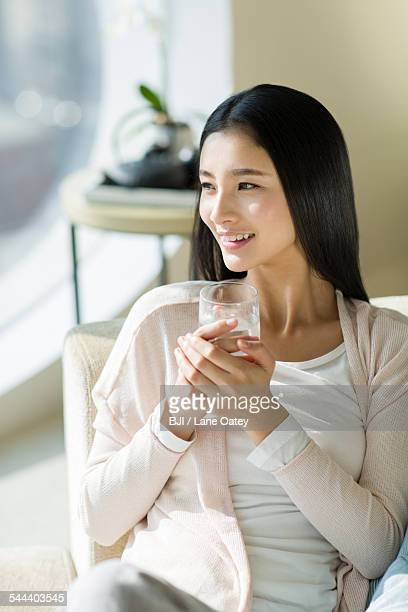 Happy young woman drinking water on sofa
