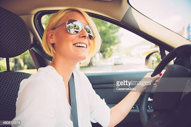 Happy Young Woman Driving a Car in the City