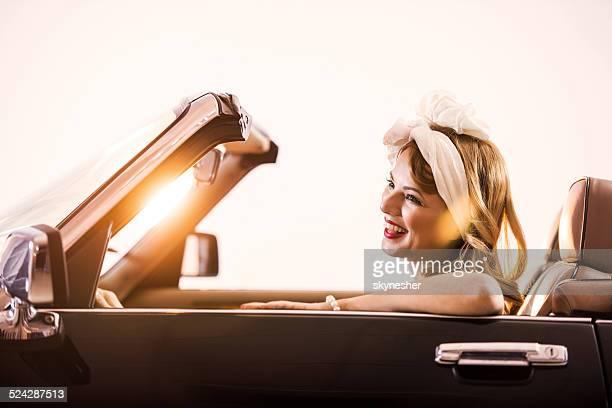 Heureuse jeune femme conduire une voiture vintage.