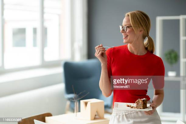 happy young woman eating a piece of cake in office - 女性建築家 ストックフォトと画像