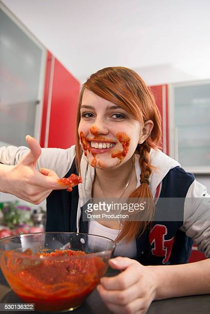 Happy young woman eating tomato sauce in kitchen, Munich, Bavaria, Germany