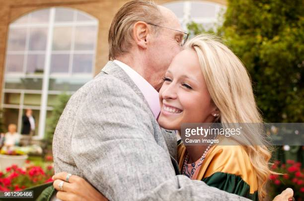 happy young woman embracing father at campus - pareja hombre mayor y mujer joven fotografías e imágenes de stock