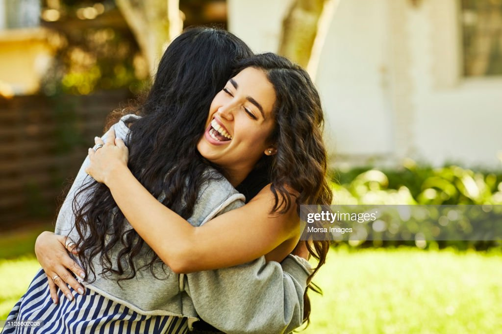 Happy young woman embracing friend at yard : Stock Photo