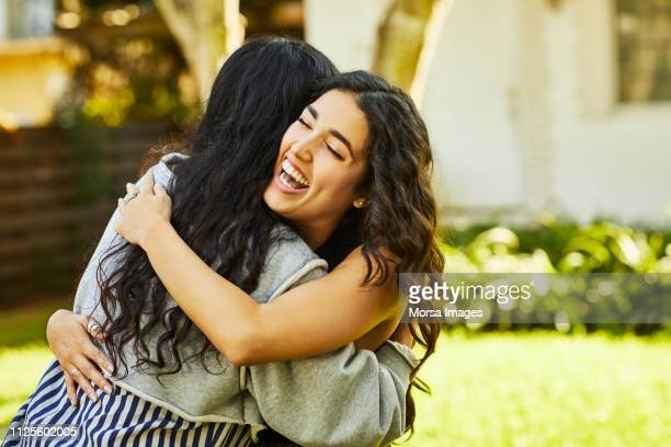 happy young woman embracing friend at yard - embracing stock pictures, royalty-free photos & images
