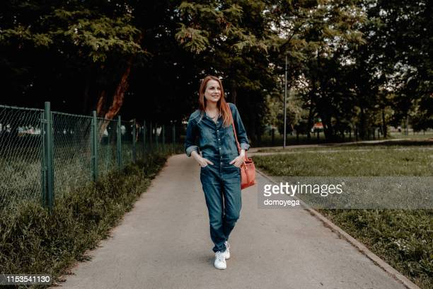 happy young woman enjoying a walk in the park - jumpsuit stock pictures, royalty-free photos & images