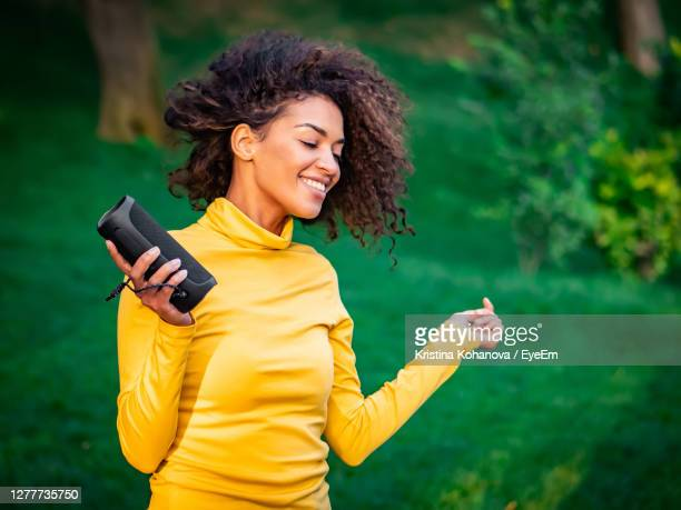 happy young woman enjoying music in park - bluetooth stock pictures, royalty-free photos & images