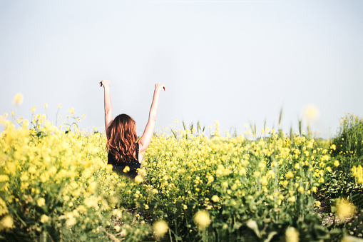 happy young woman enjoying summer in yellow field at sunset - gettyimageskorea