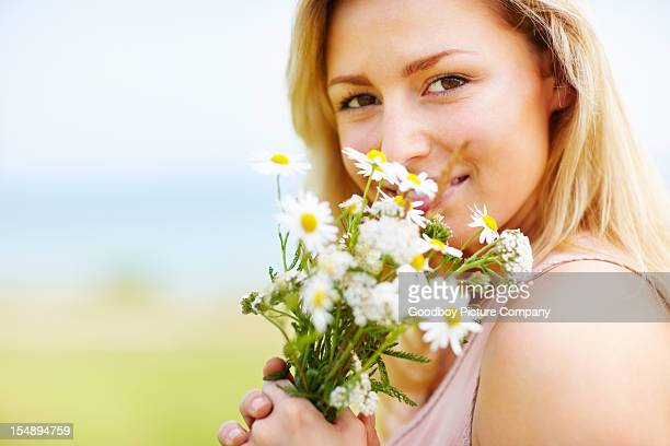 Happy young woman enjoying the fragrance of flowers