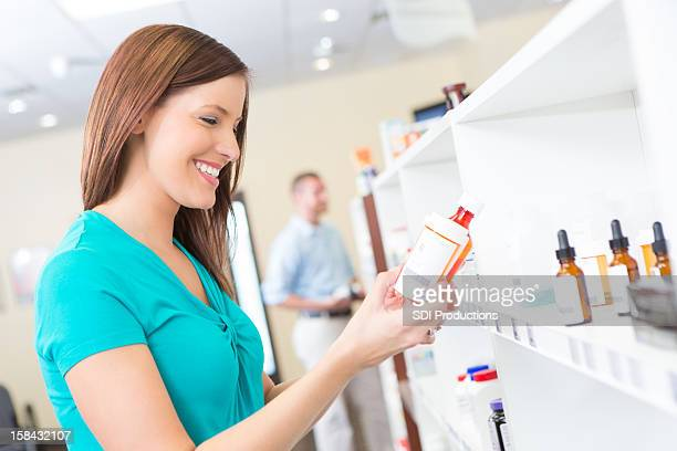 Happy young woman examining medicine at the pharmacy