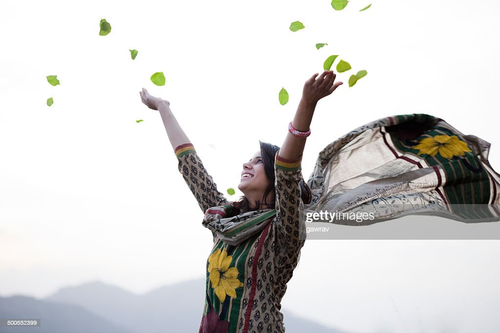 Happy young woman flying leafs in air towards sky. : Stock Photo