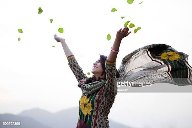 Happy young woman flying leafs in air towards sky.