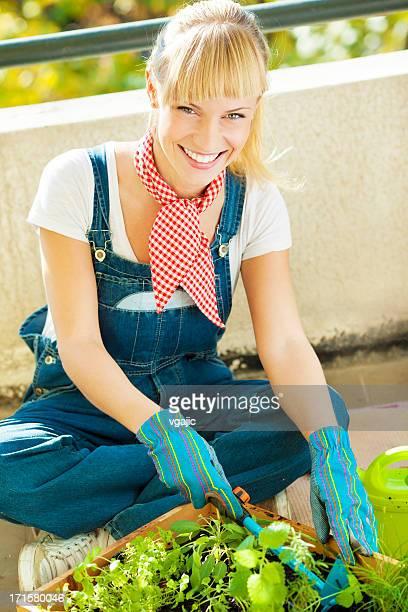 Glückliche junge Frau, die Gartenarbeit auf einen Balkon.