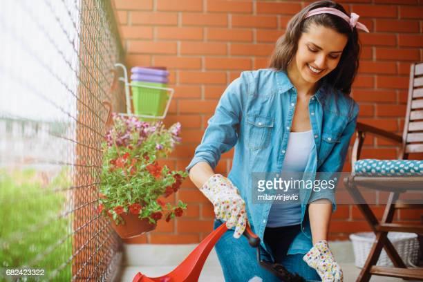 Glückliche junge Frau im Garten auf dem Balkon