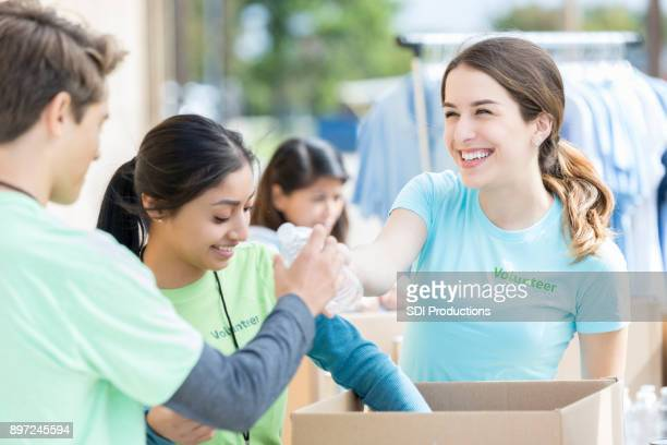 Happy young woman hands water bottle to friend during food drive