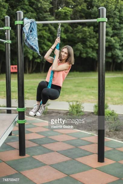 happy young woman hanging from rope of jungle gym at park - schommelen bungelen stockfoto's en -beelden