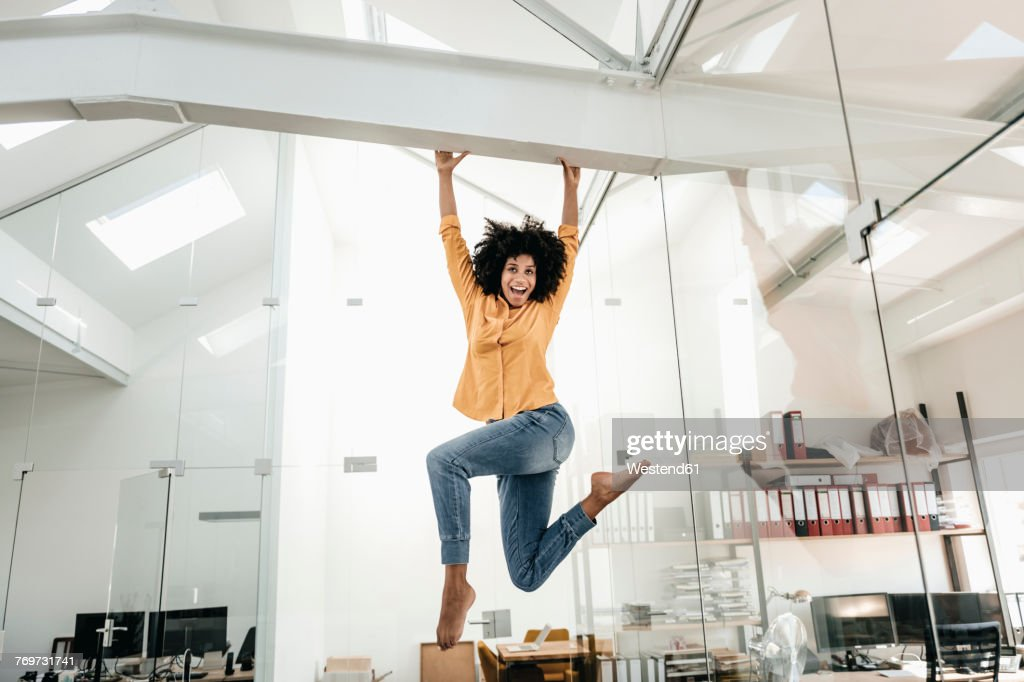Happy young woman hanging on beam in office : Stock Photo