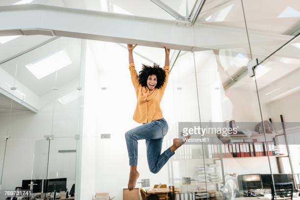 happy young woman hanging on beam in office - afro frisur stock-fotos und bilder
