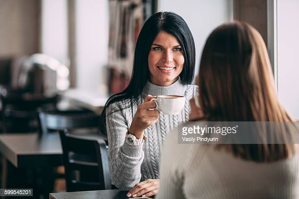 Happy young woman having coffee with female friend in cafe