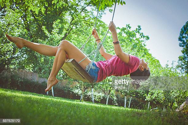 Happy young woman having fun on a swing in park