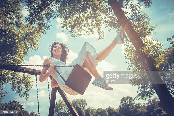 happy young woman having fun on the swing - swinging stock pictures, royalty-free photos & images