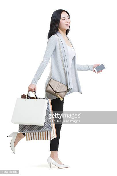 Happy young woman holding a smart phone and shopping bags